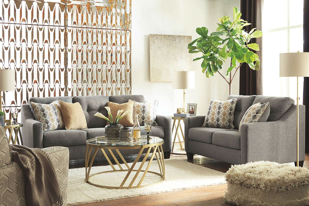 Mid-century modern-inspired living room with grey sofa and yellow accent pillows