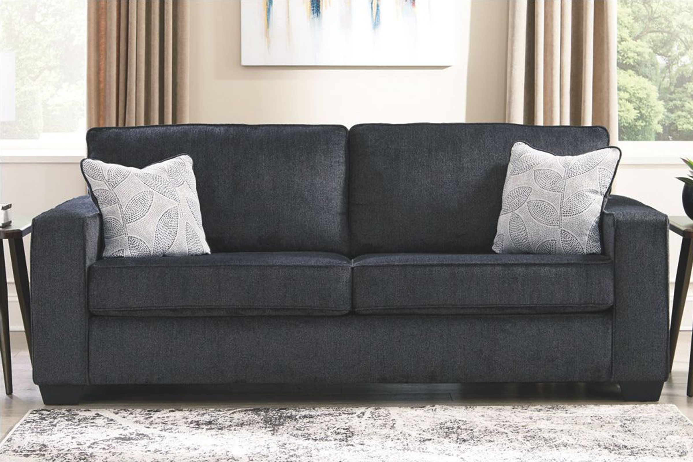 Dark grey (with a blue undertone) sofa with square arms and 2 toss pillows with blue plant pattern