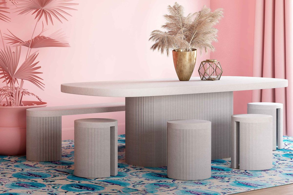 Grey concrete dining set with fluted base on table and stools in a light pink room